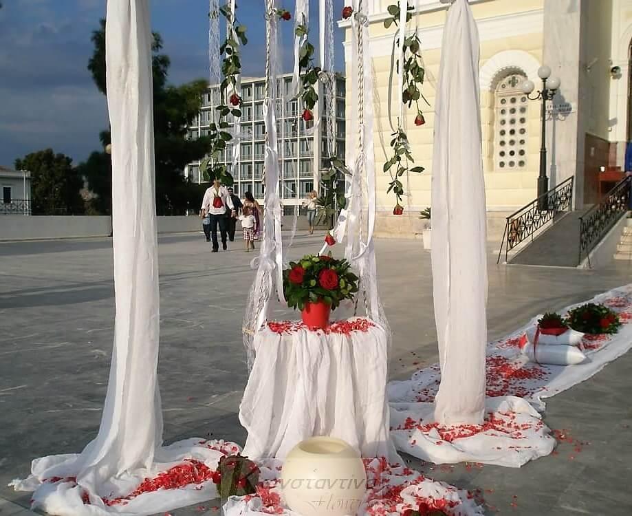 Στολισμός εκκλησίας με κόκκινες συνθέσεις λουλουδιών από το Konstantina Flowers