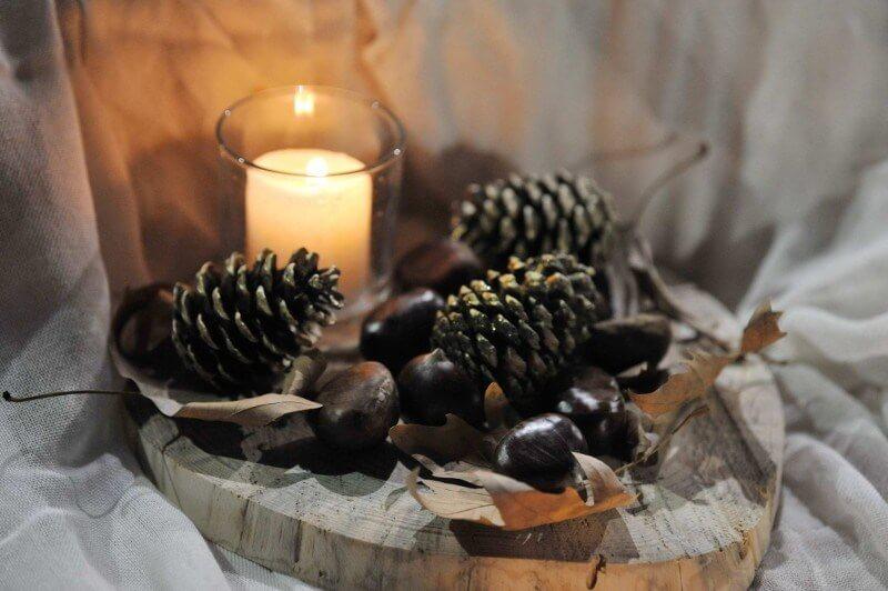 """Χριστουγεννιάτικος στολισμός πάνω σε κορμό ξύλου, με κεράκι σε γυάλα και κουνουνάρια από το """"Ευχές με Πεταλούδες"""""""